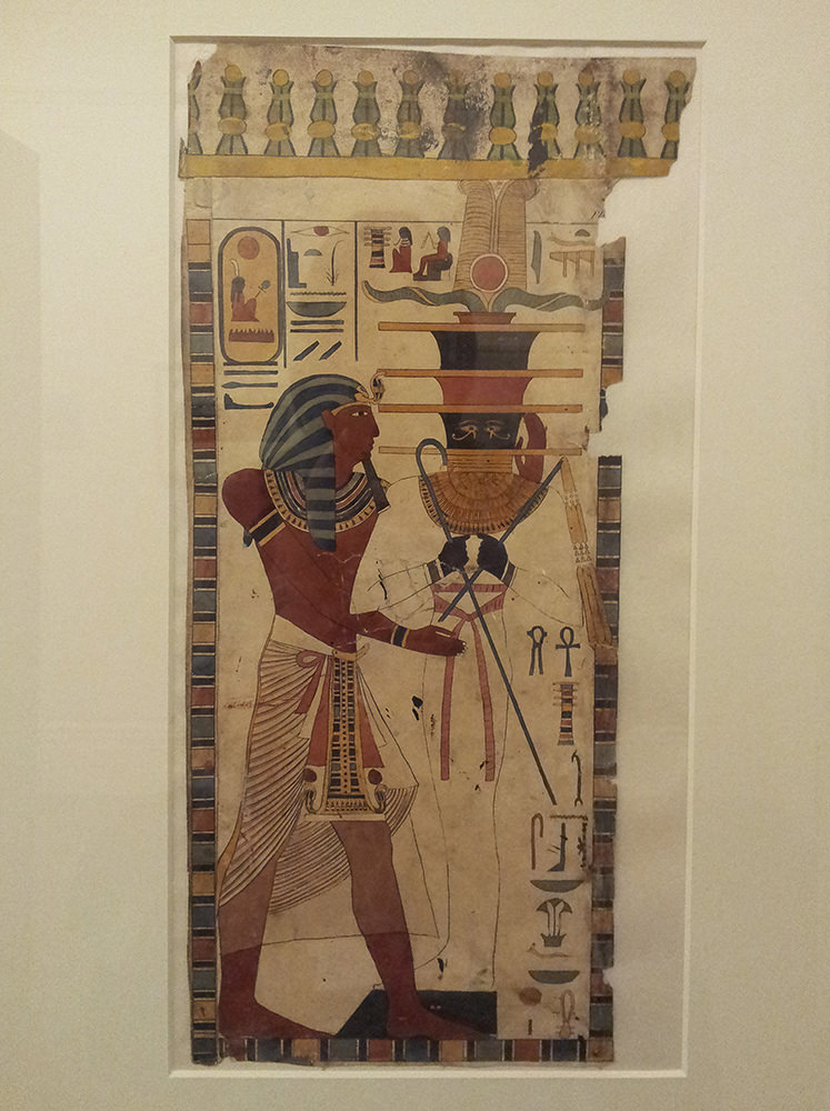Seti wearing a white kilt and Nemes-headdress standing before Osiris as a mummy with a djed-shaped head