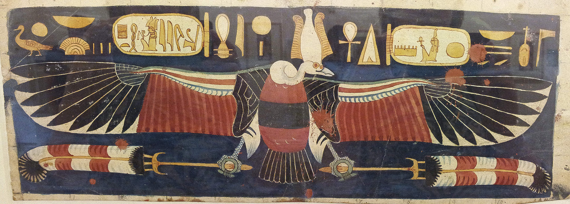Nekhbet as a vulture, with outstretched wings and wearing an Atef crown. She has hieroglyphs either side of her, running along above her wings