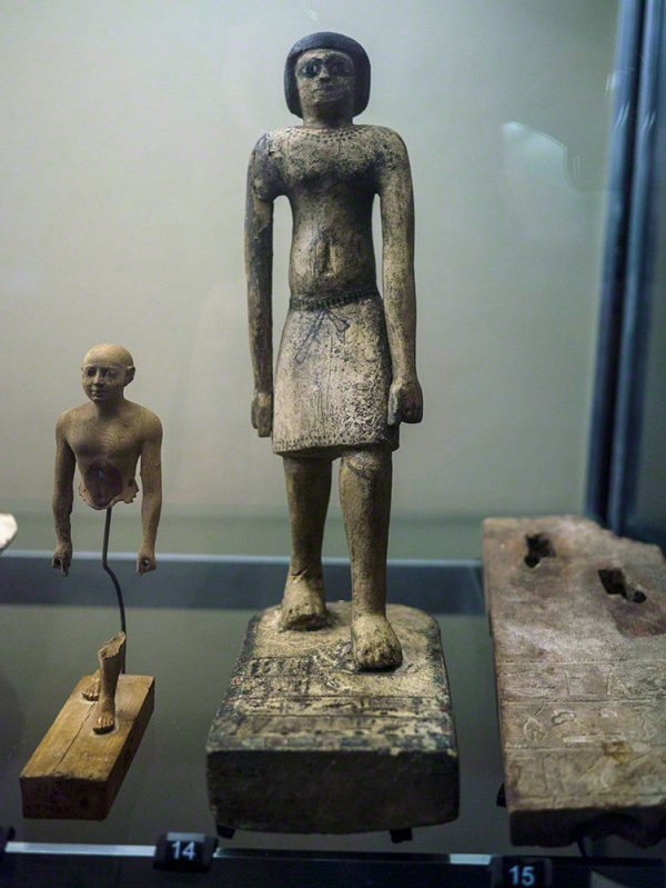 A wooden statue with paintwork still visible, including the tie on the kilt and the necklace. It also has an offering formula down its back. Unprovenanced (Acc. No. E.8129)