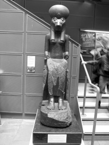 A front view of the left-hand Sekhmet, seated next to the main staircase. She's suffered damage, particularly in the area around her lower legs and forearms