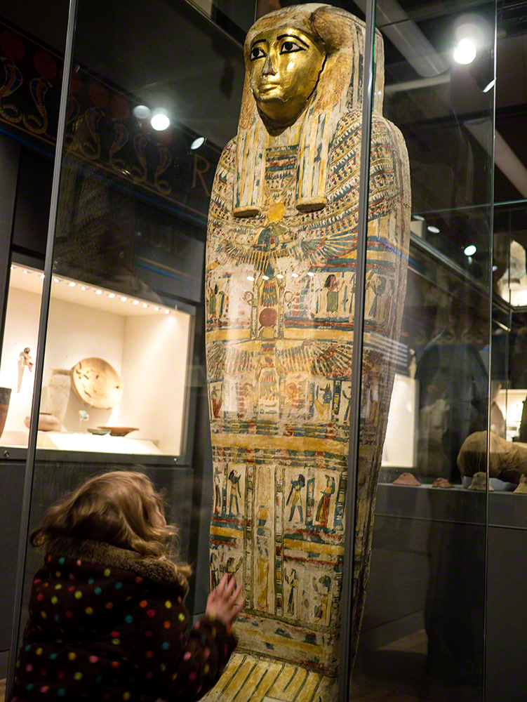 The young girl looking up at a coffin lid which is stood up on its end