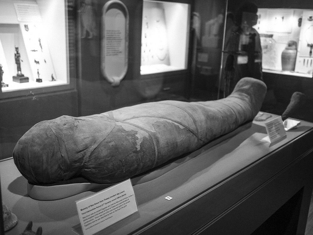 The wrapped mummy is lying out in a glass case in the centre of the room