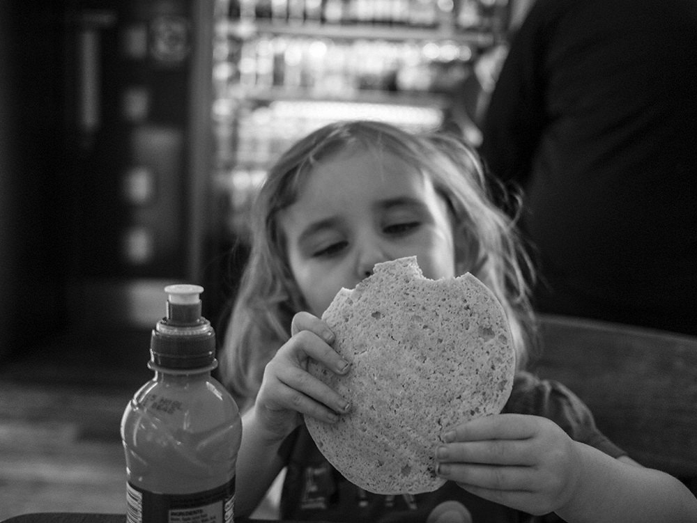 A young girl sitting in a cafe with her face partially obscured by a large, round cookie