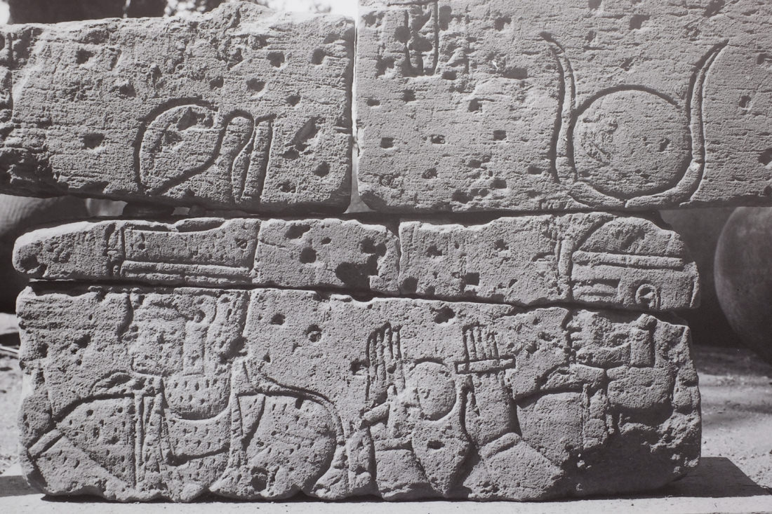 A closeup of a photo of fragments of temple wall pieced back together. It shows the head and shoulders of a king - shown by his wearing the double crown of Egypt - with a goddess behind him. She wears a headdress of a sundisk and cow horns, and she has her hands up in adoration