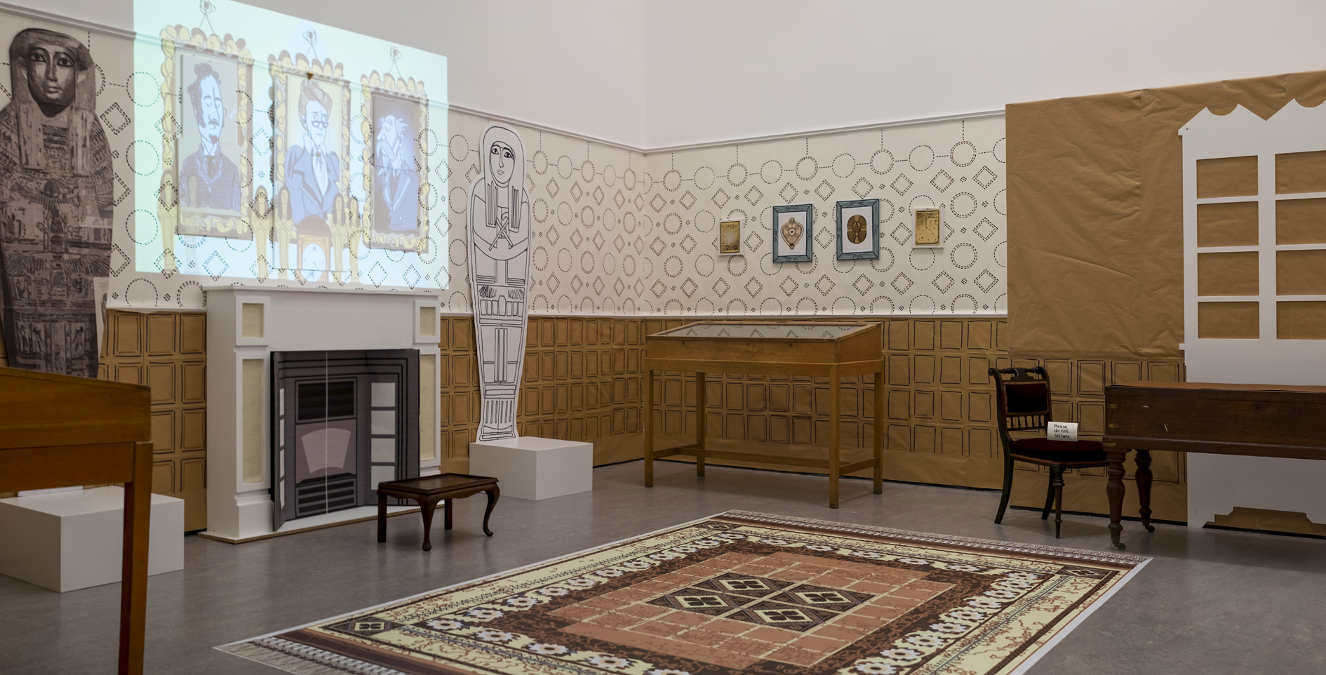 A large room with a fireplace, table and chair and a couple of wooden display cases containing artefacts. There are paper mockups of Egyptian coffins either side of the fireplace and cartoon-style portraits being projected onto the wall above the fireplace