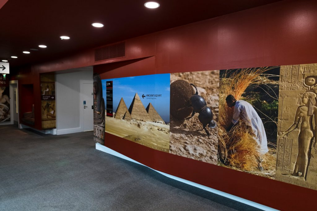 The corridor with the entrance to the gallery. There are photos of Egypt, such as the pyramids and a farmer gathering crops