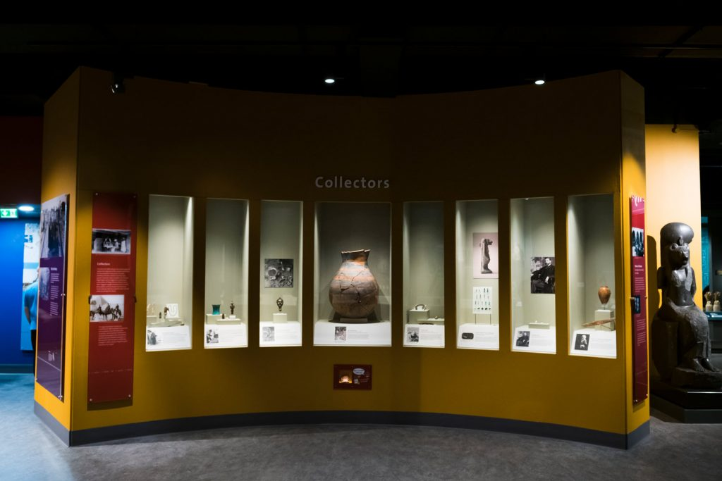 Looking at a yellow, curved display case entitled 'Collectors'. There are eight tall, rectangular windows, each with a small number of artefacts displayed in each one. The centre window has a large, ceramic container in it