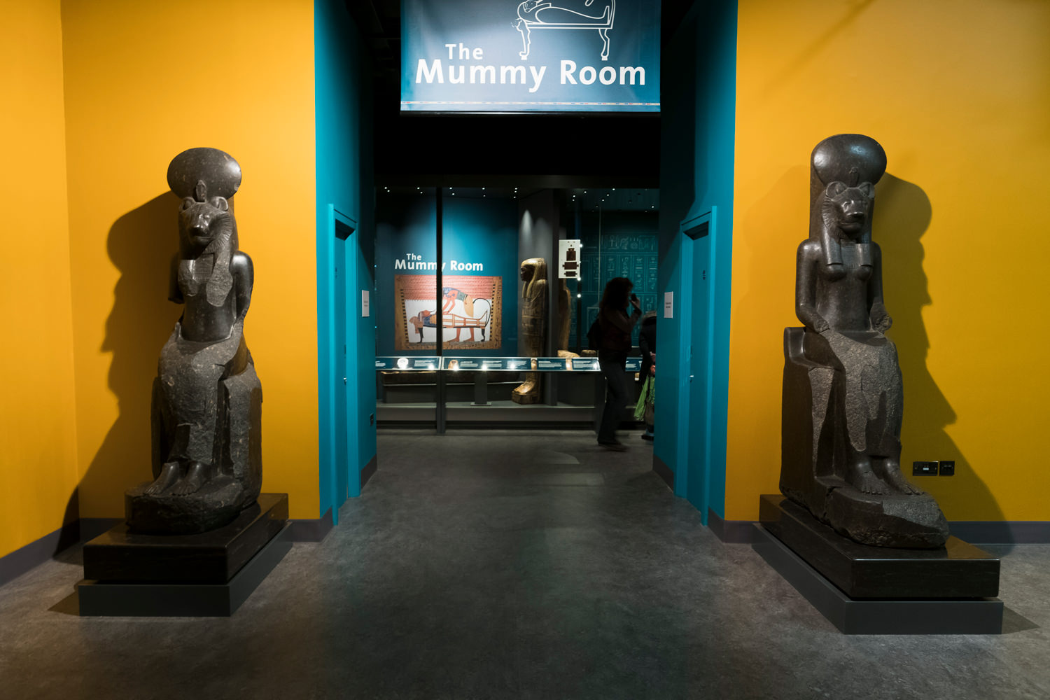 The entrance to the mummy room. The museum's two large, stone statues of the goddess Sekhmet are either side of the doorway.