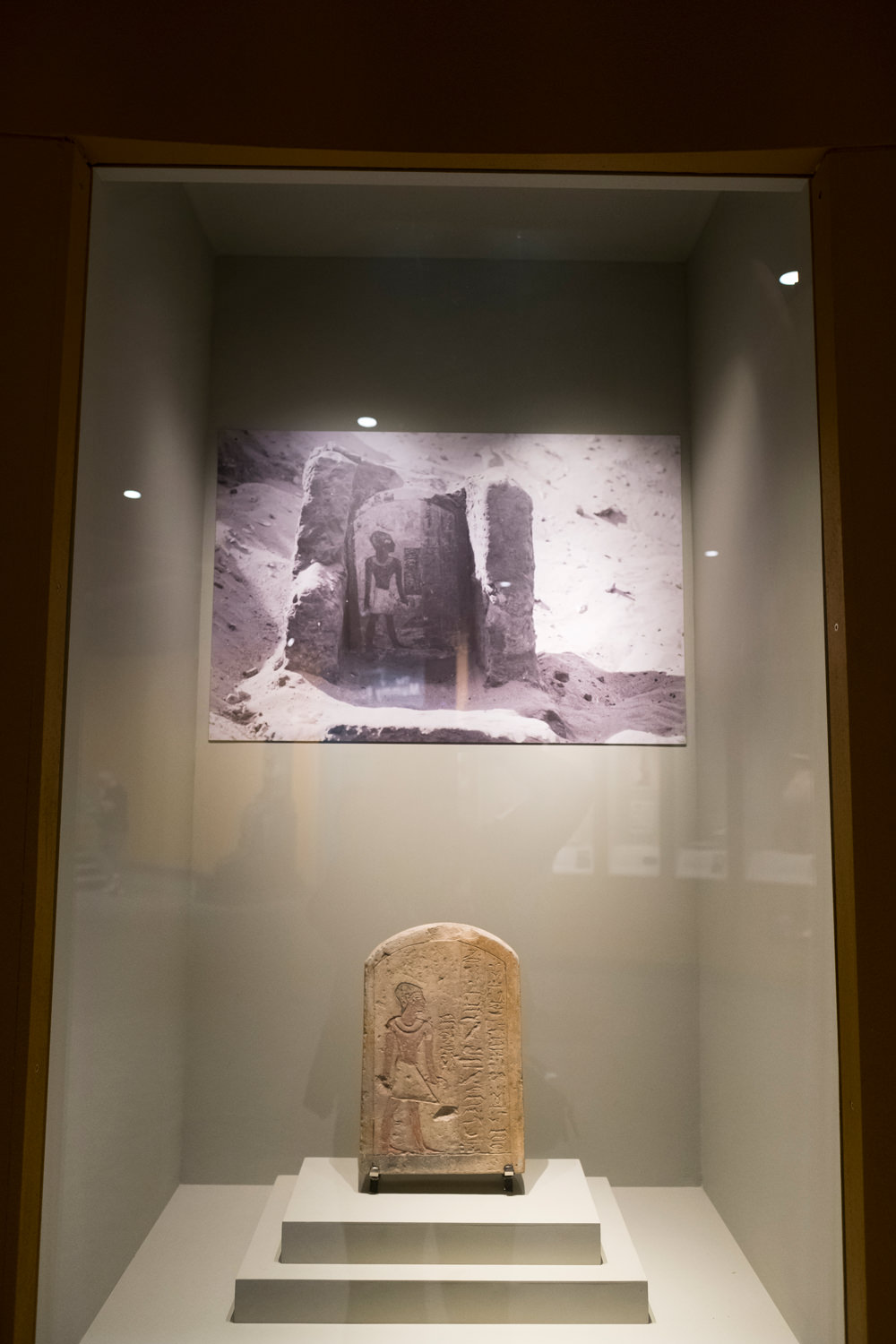 A carved, painted funerary stela in a display case with an old photo of it in situ when it was first discovered above it