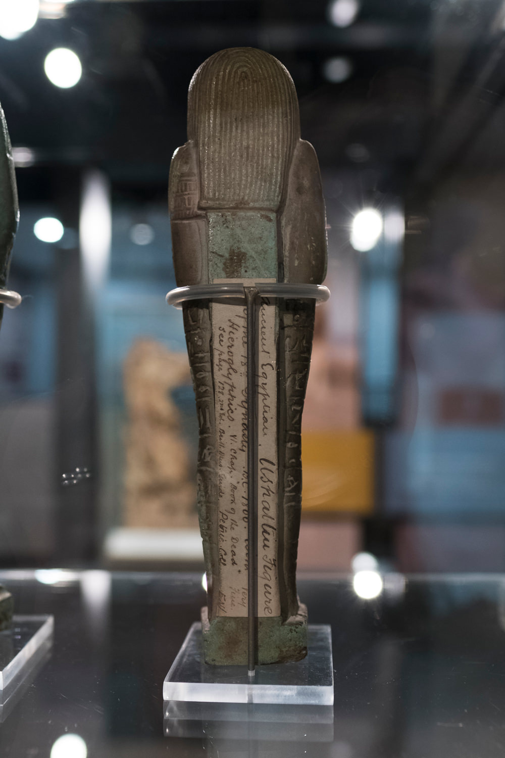 A shabti viewed from the back. It has an old, handwritten label in beautiful cursive script, from many years ago