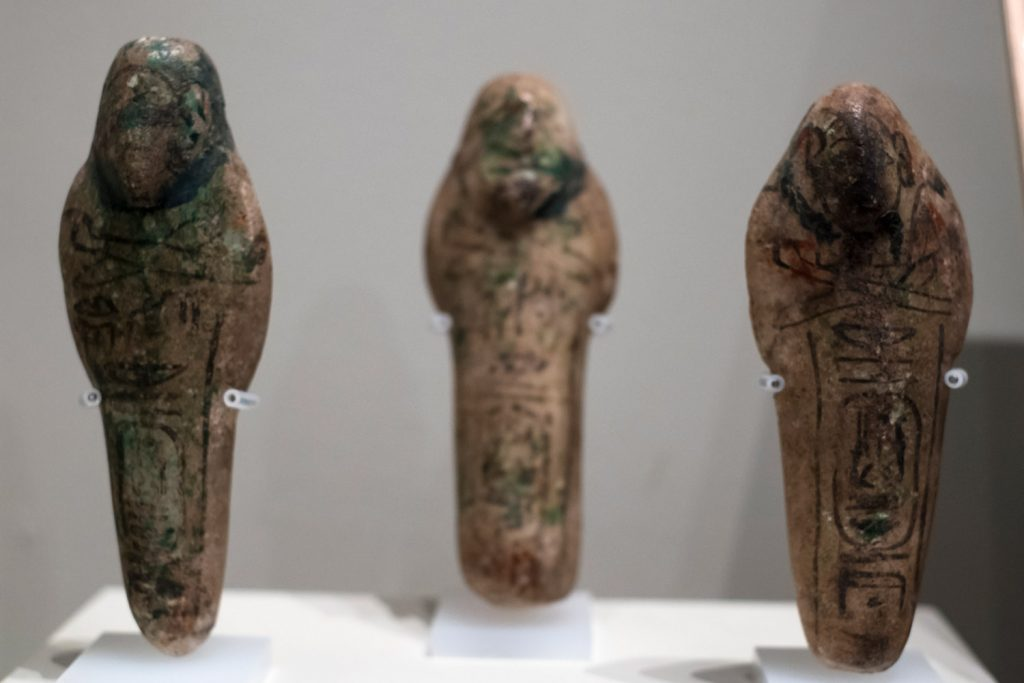 Three small shabtis. Unlike many shabtis that are beautifully carved and inscribed, these are crudely shaped, with the text, faces and arms painted on in black ink