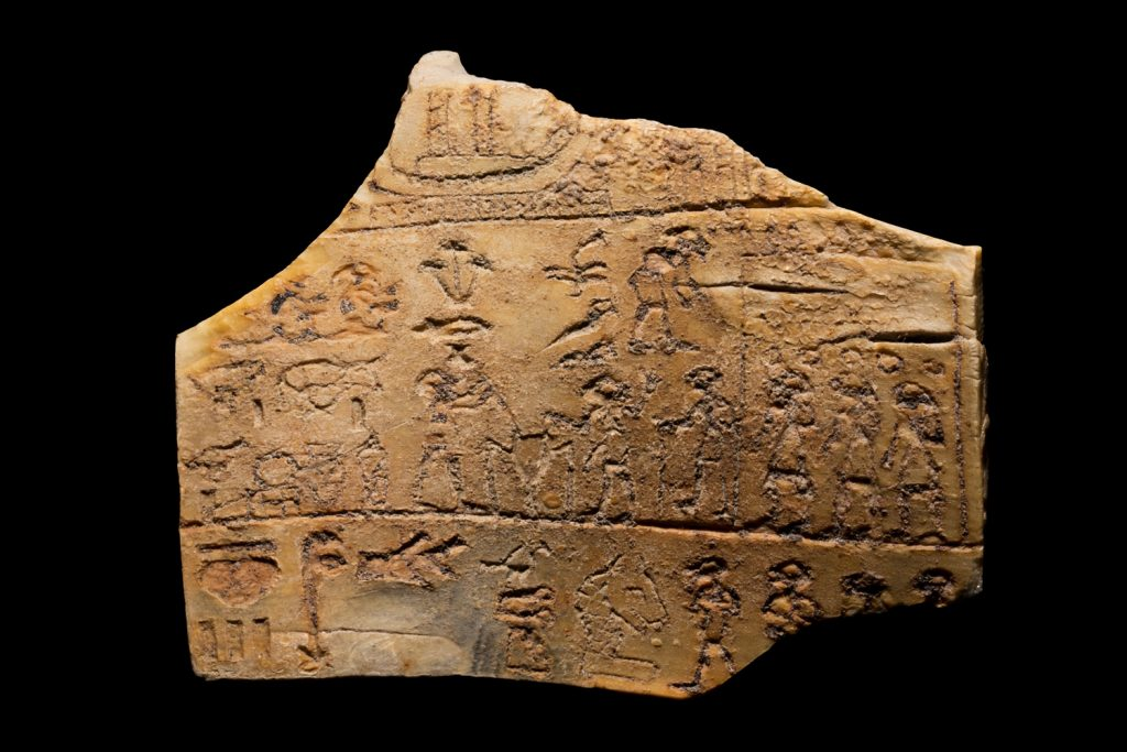 A small, rectangular ancient Egyptian ivory label with hieroglyphs