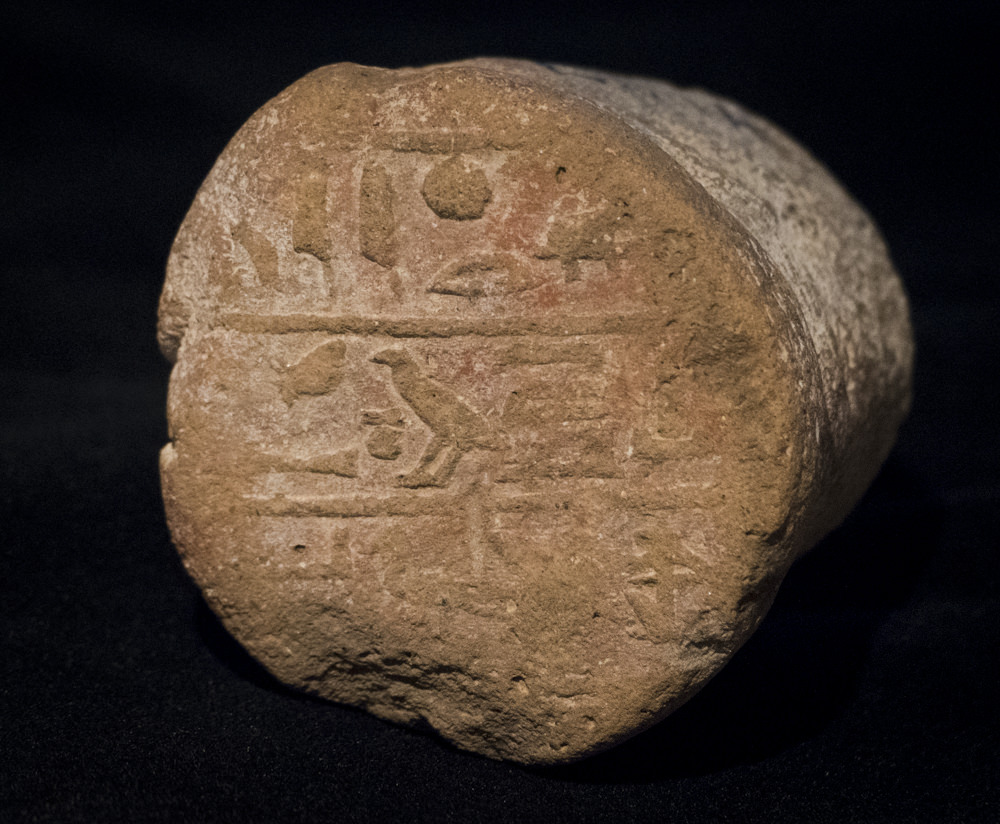 An ancient Egyptian funerary cone with a hieroglyphic inscription on the end