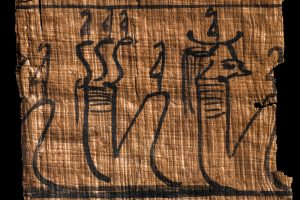 Two ancient Egyptian judgement deities as seated humans, one with a cow's head, the other with a three snakes' heads