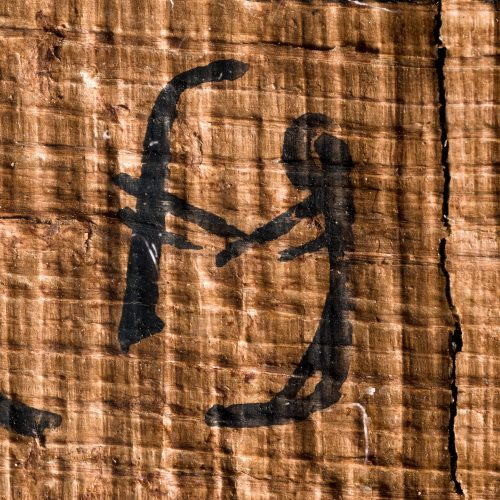 A cursive hieroglyph of a man holding stick out in front of him