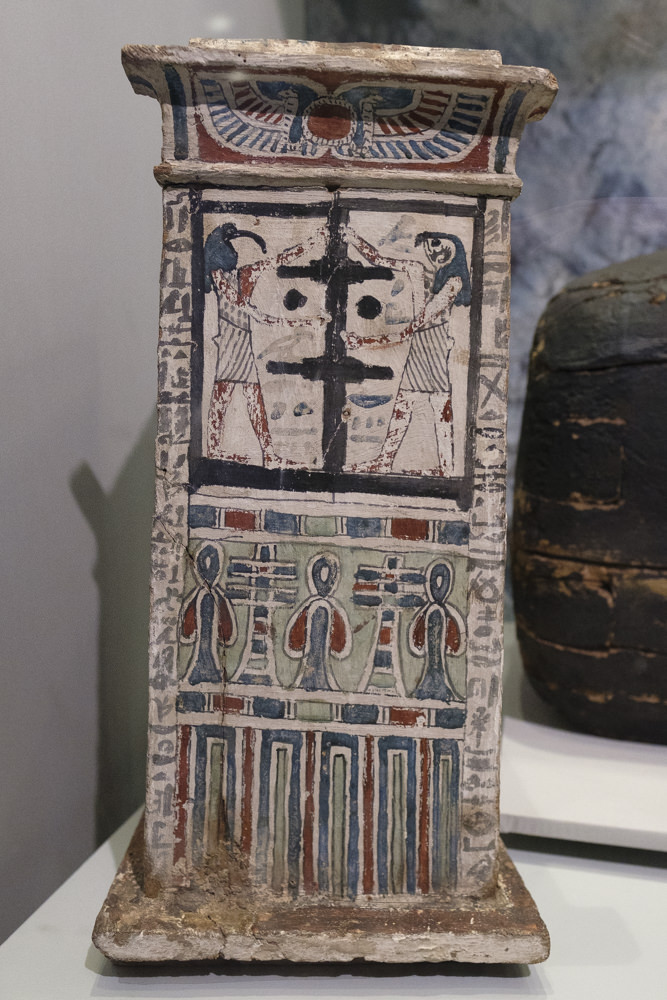 A tall, rectangular Canopic chest covered with painted decorations