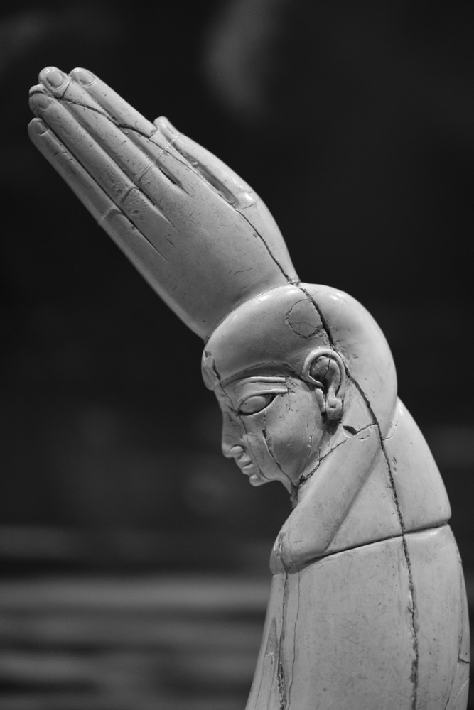 The top half of an ancient Egyptian ivory clapper, carved into the shape of a head and hand