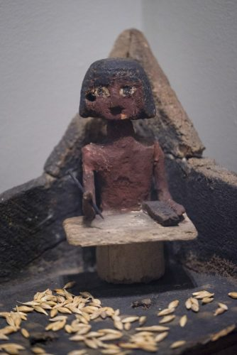 An ancient Egyptian wooden scribe sitting in the corner of a granary with his pen, palette and paper on his knees
