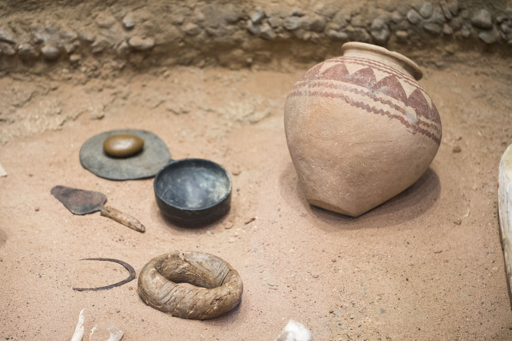 Predynastic Egyptian pots and a pot stand sitting in sand
