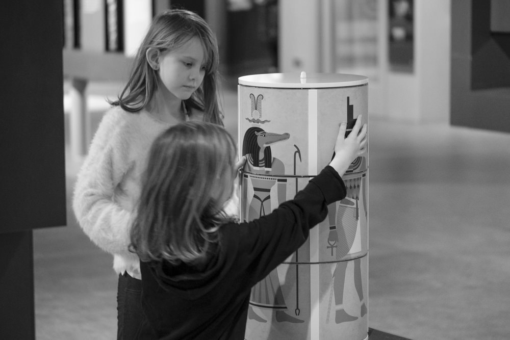 Two girls making Egyptian gods in a museum gallery