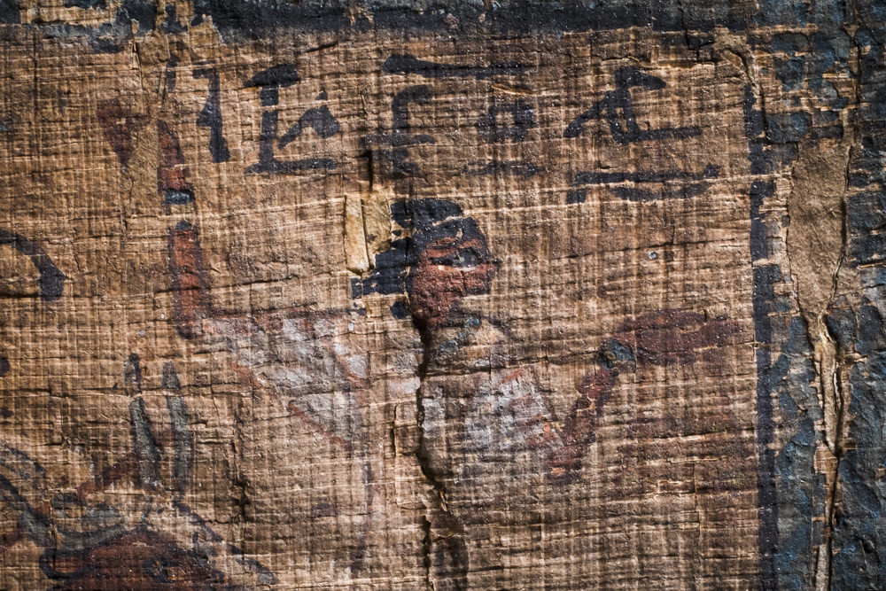 A close-up of an ancient Egyptian person painted on papyrus