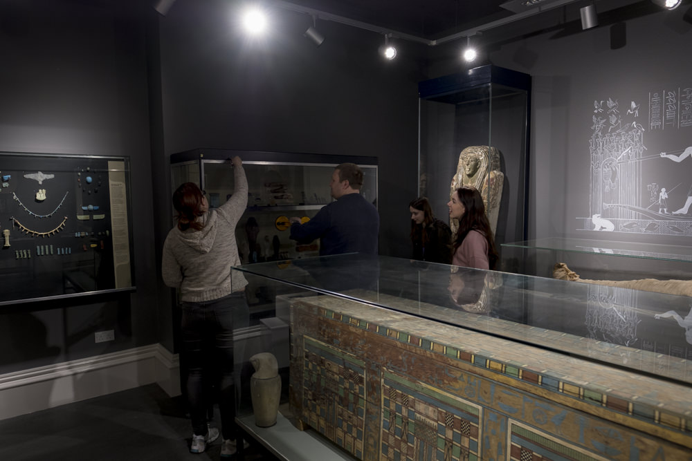 Four people in a museum gallery removing the glass from the front of a display case