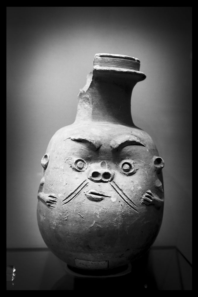 A round jar with a tall neck. The face of the god Bes is carved fairly crudely into the clay. He also has small hands and ears.