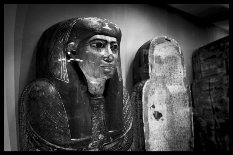 The top part of the coffin, which has a carved face in classic Egyptian style, with a large, black wig and headdress.