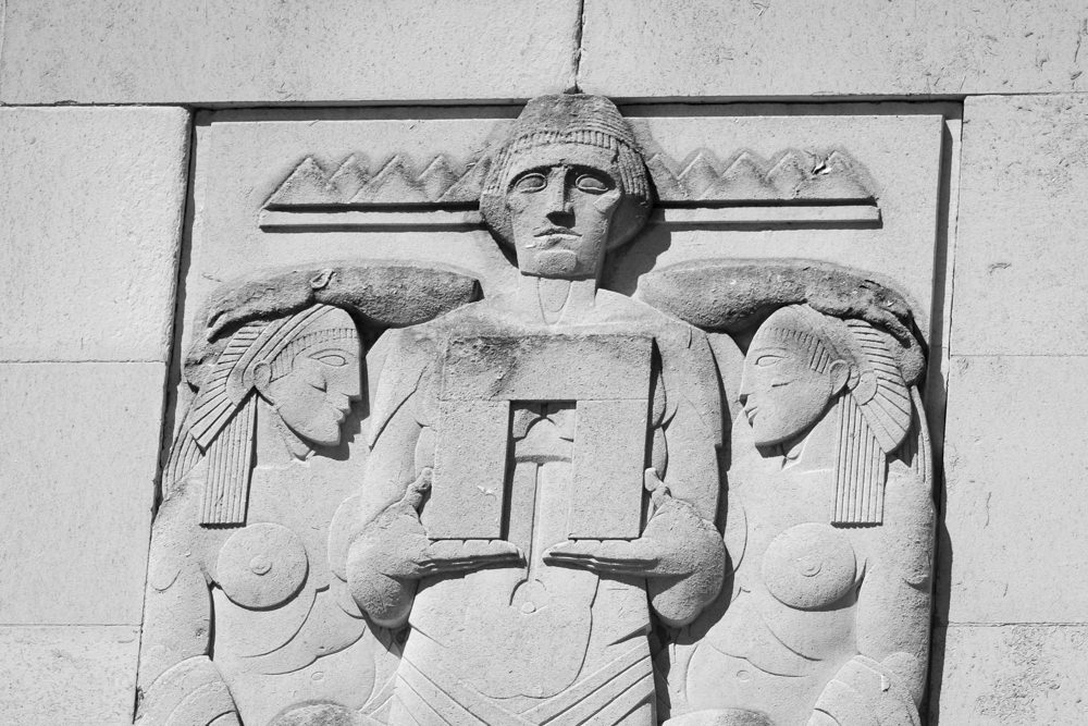 A stone carving of three people; a man and two women. The women have Egyptian hairstyles