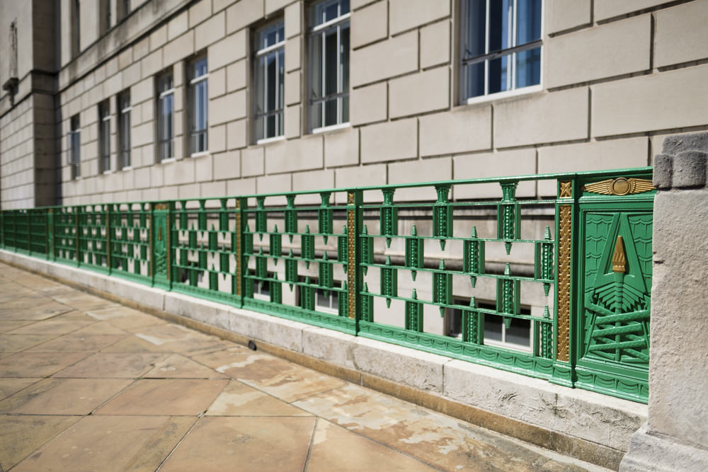 A green and gold fence with art deco Egyptian revival design