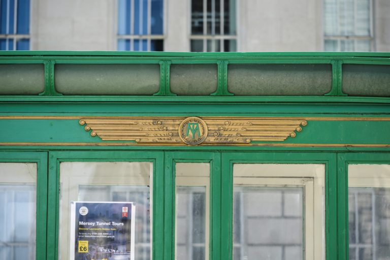A green and gold toll booth with a winged emblem on the side