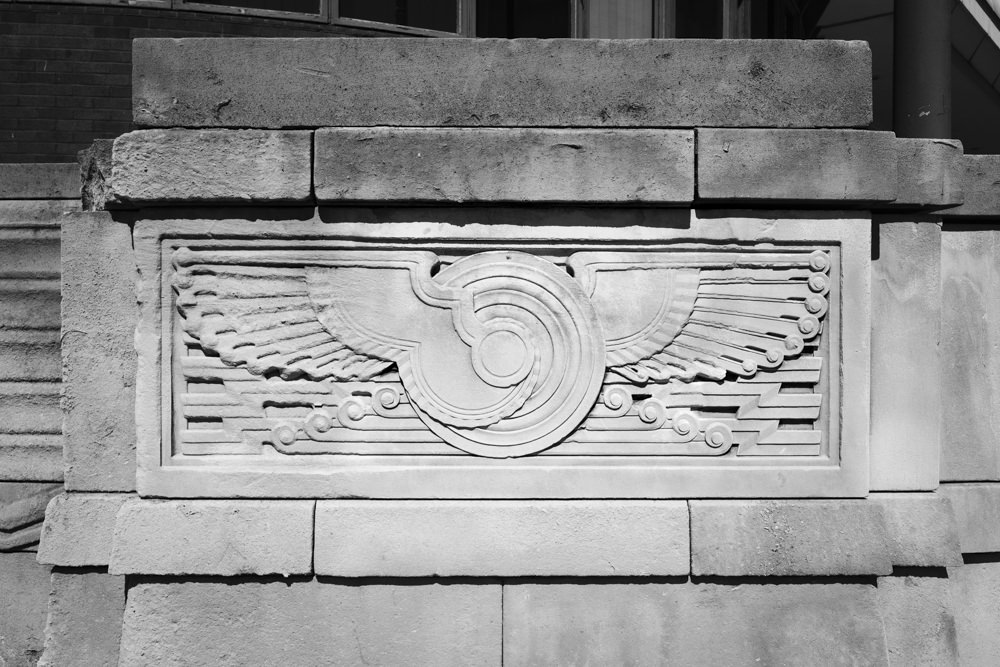 An art deco-style winged sundisk carved into the side of a stone wall