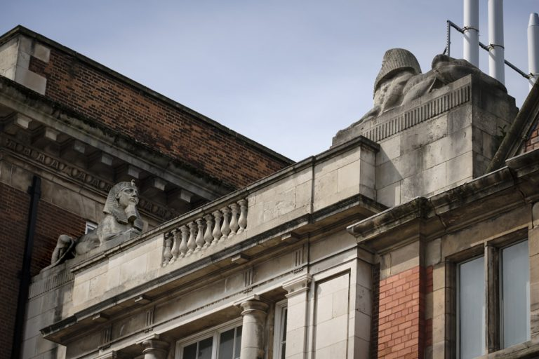 Two Egyptian revival sphinxes atop a building at the University of Liverpool