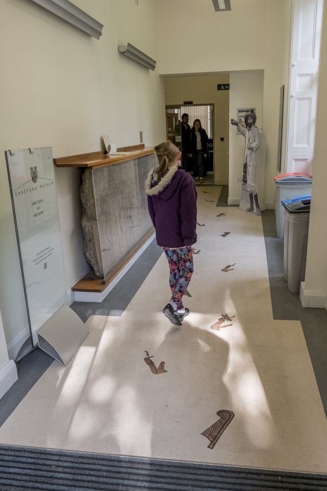 A girl approaching the door to a museum