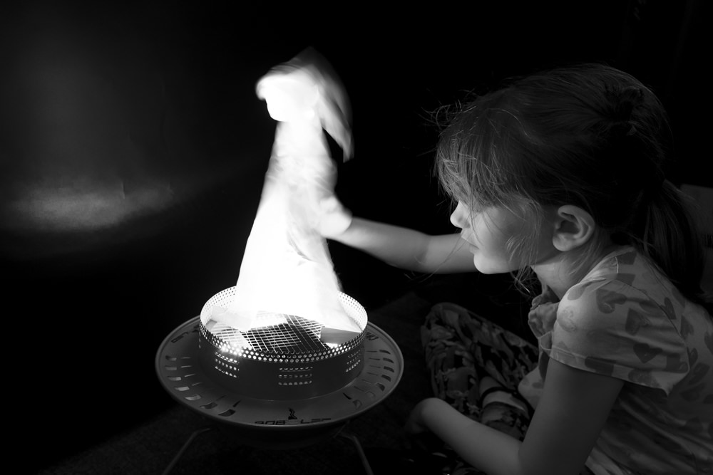 A girl playing with a pretend flame