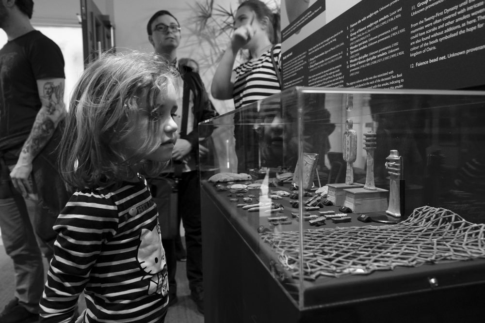 A girl looking at a display case of ancient Egyptian amulets