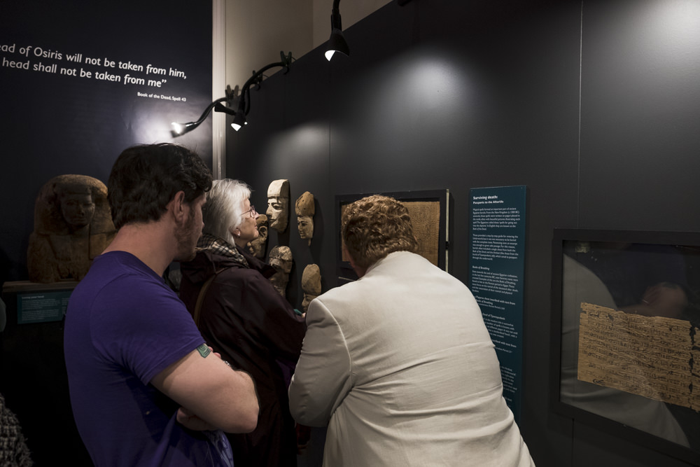 People looking at a sheet of ancient egyptian papyrus on display