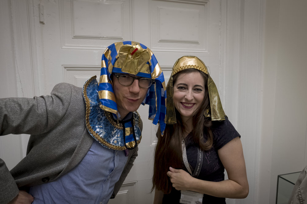 Two very grown-up Egyptologists wearing children's dress-up pharaoh's headdresses