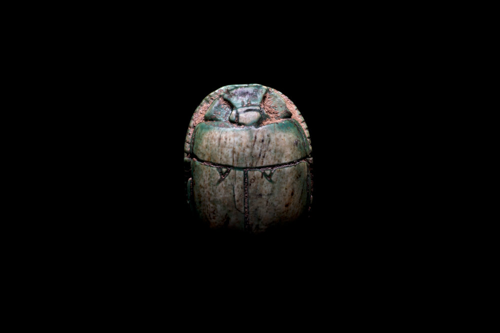A small, wingless ancient Egyptian scarab beetle representing the god Khepri