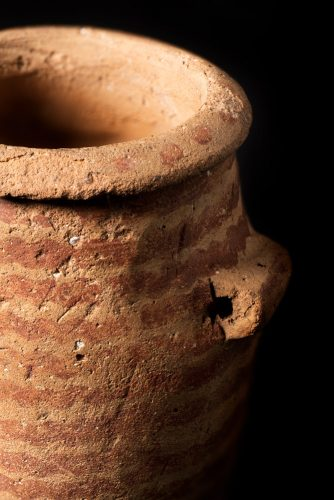 The top of a small, cylindrical ceramic pot from Predynastic Egypt with red wavy parallel lines painted around the outside