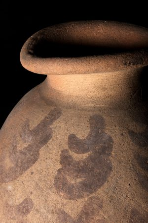 The top section of a ceramic pot from ancient Koshtamna with red painted curved patterns