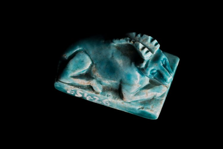 A small, ancient Egyptian amulet of an ibex lying on the ground