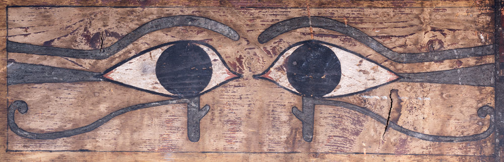 A pair of ancient Egyptian eyes painted on the side of a wooden coffin