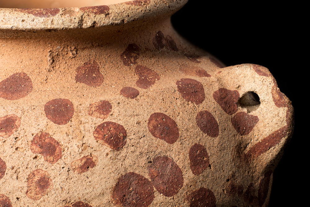 The side of a small, round pot with a lug-shaped handle from Predynastic Egypt