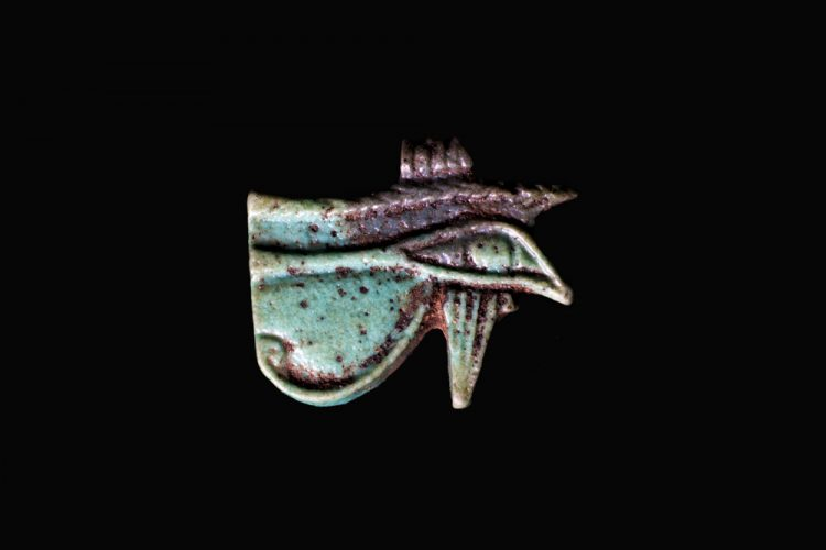 A small, ancient Egyptian faience amulet of the Eye of Horus