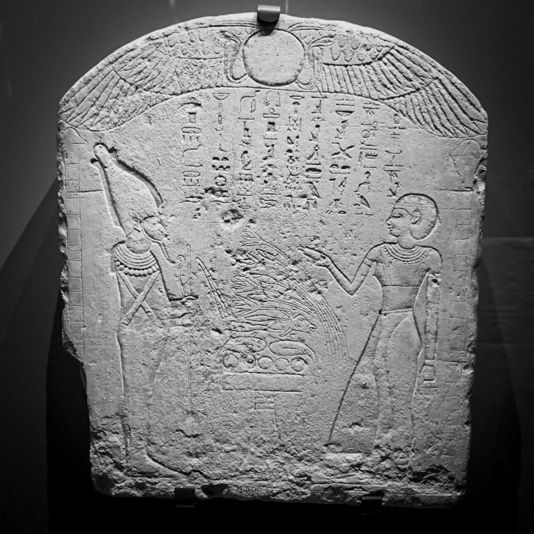 A rectangular, round-topped stela with a carved hieroglyphic inscription and illustrations