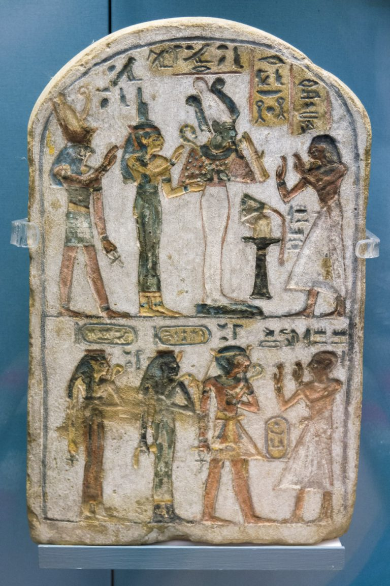 A small, rectangular, round-topped stela. It has two images on it - on the top is the three deities and the owner. On the bottom half the owner is worshipping three deceased members of the royal family.