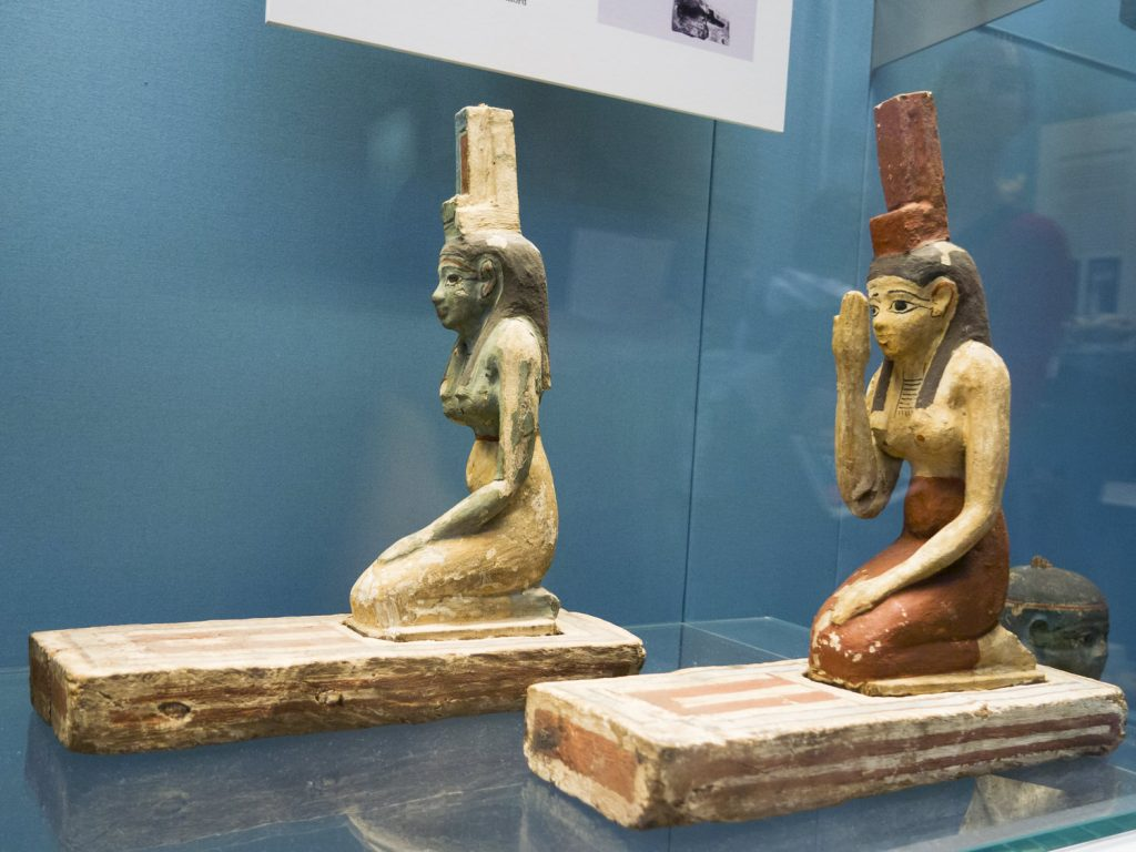 Two statues of Isis, kneeling down, with a throne emblem on her head