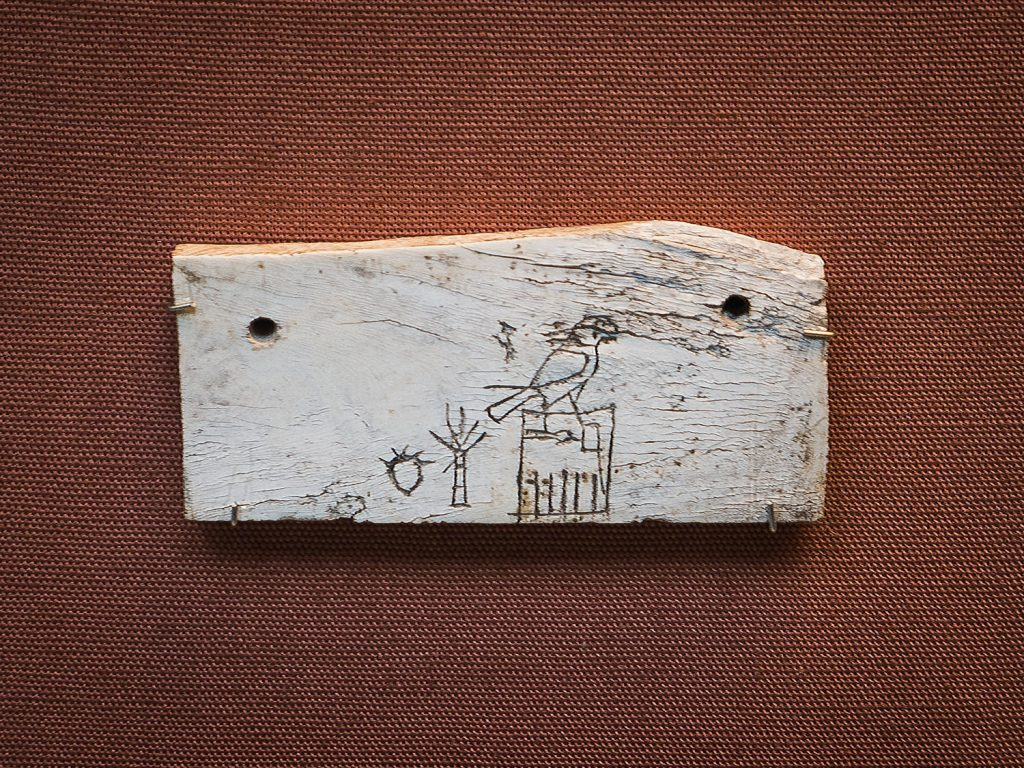 A small rectangle of ivory with a rough hieroglyphic inscription of a pharaoh's name