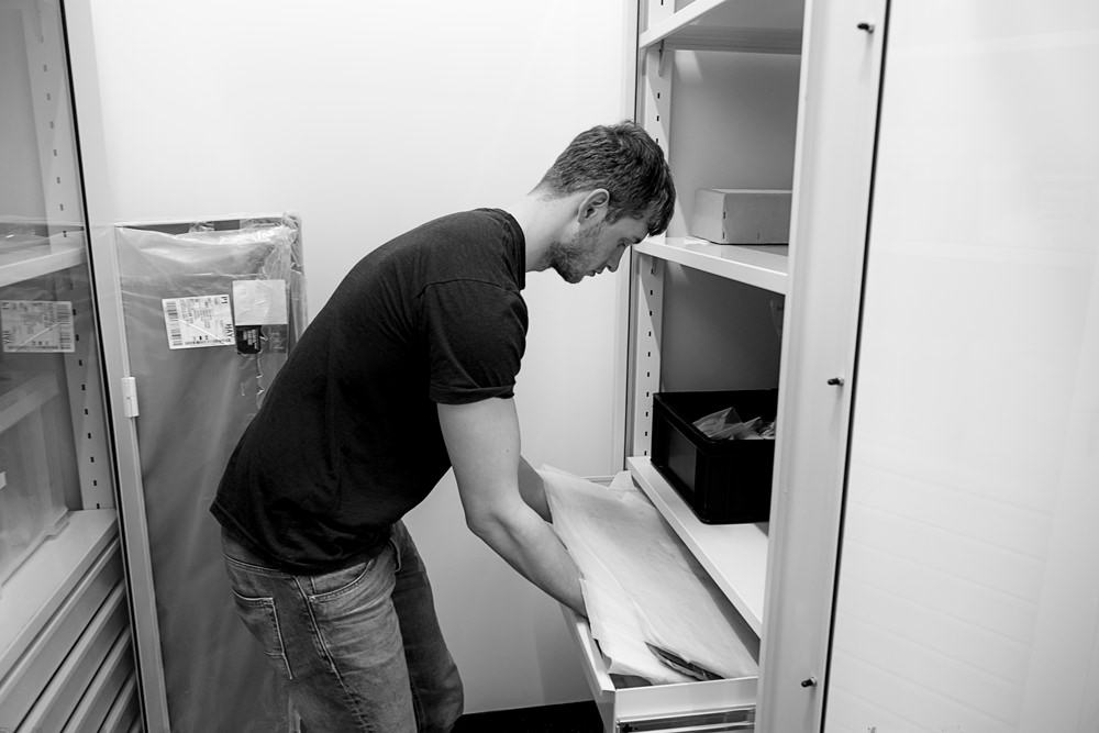A man getting a piece of papyrus out of a storage drawer